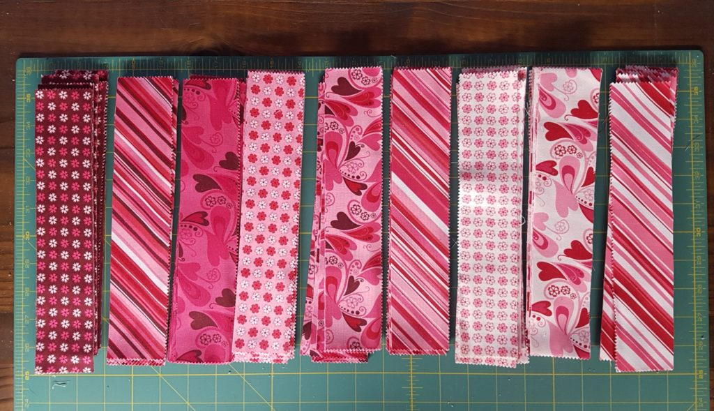 strips sorted from dark to medium to light for piecing